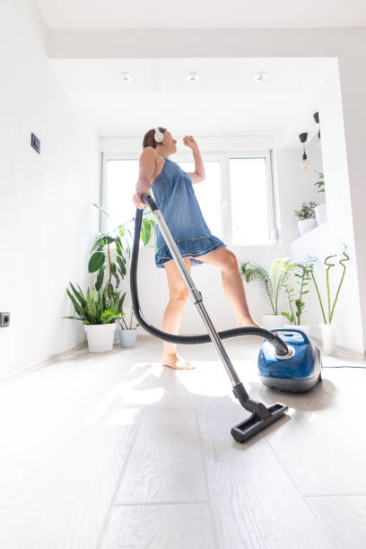 Young housewife vacuuming in the house stock photo