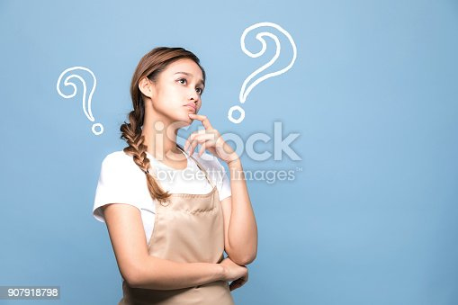 istock young housewife with question marks. 907918798