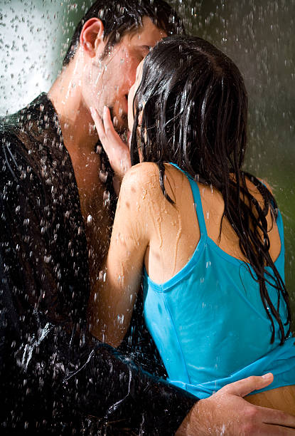 young hugging couple kissing under a rain, in passion - love at first sight stock photos and pictures