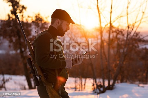 istock Young hunter using smart phone in a field 1124799674