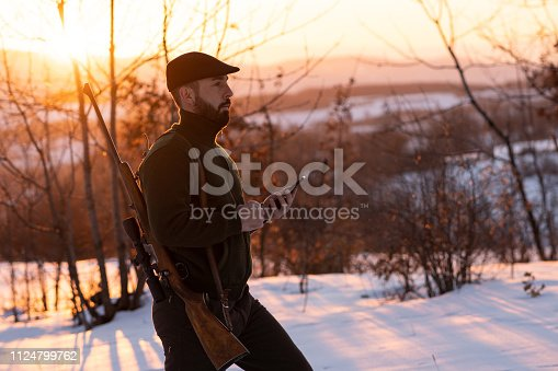 istock Young hunter using smart phone in a field 1124799762