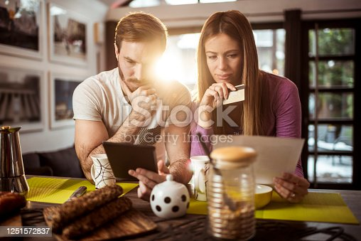 Young couple agreeing on doing some online shopping at home. Man is holding a credit card and a tablet.