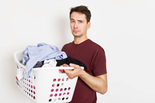 Junger Mann in Krise Hausarbeit. Nahaufnahme eines gestressten Mann mit Korb voller Kleidung – Foto