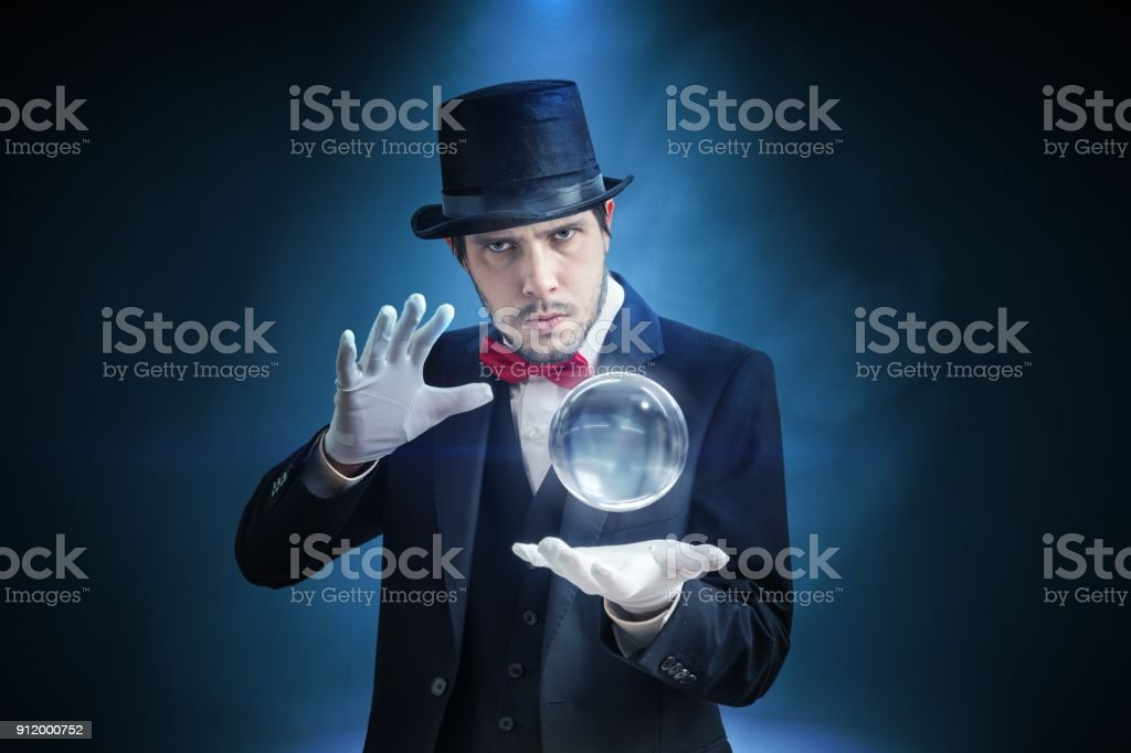 Young illusionist, magician or fortune teller is predicting future with crystal sphere. stock photo