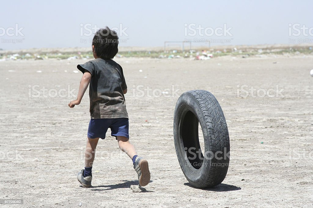 Young impoverished boy playing with a car tire on dirt patch stock photo