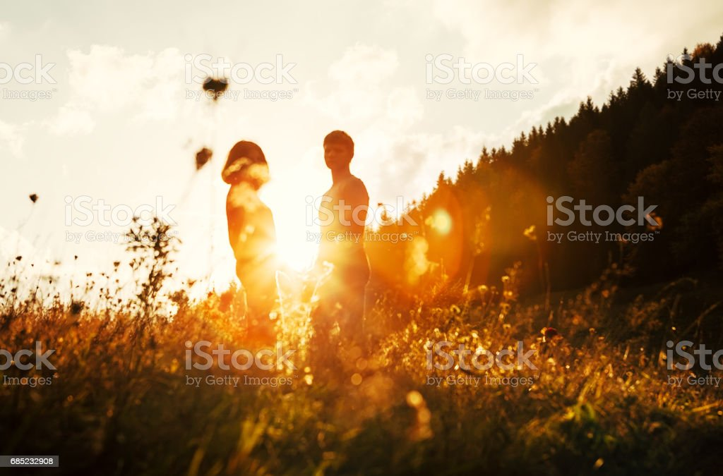 Young in love couple stay on meadow in bright sunset light royalty-free stock photo