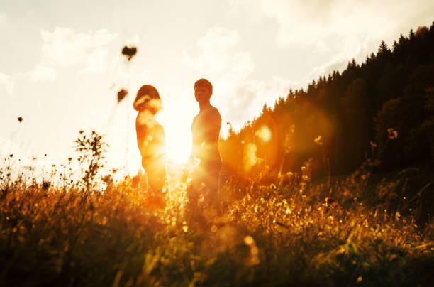 Young in love couple stay on meadow in bright sunset light Young in love couple stay on meadow in bright sunset light romance stock pictures, royalty-free photos & images