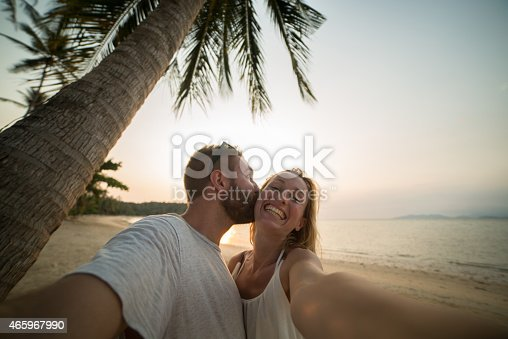Happy young couple on an exotic beach taking a selfie using a smart phone at sunset.