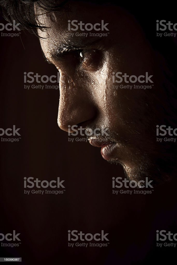 Young Indian angry man sweating over dark stock photo