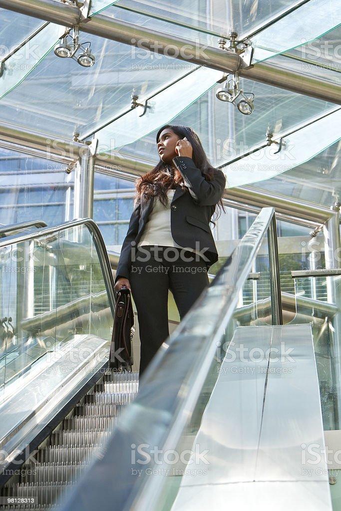 젊은 인도어 아시아판 치도 휴대전화 및 에스컬레이터 royalty-free 스톡 사진