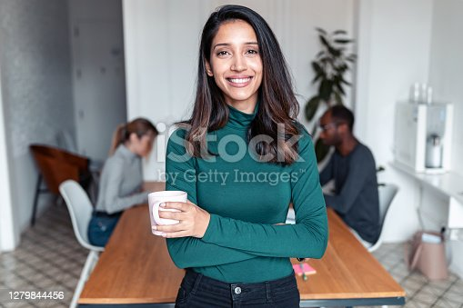 istock Young indian business woman entrepreneur looking at camera in the office. 1279844456