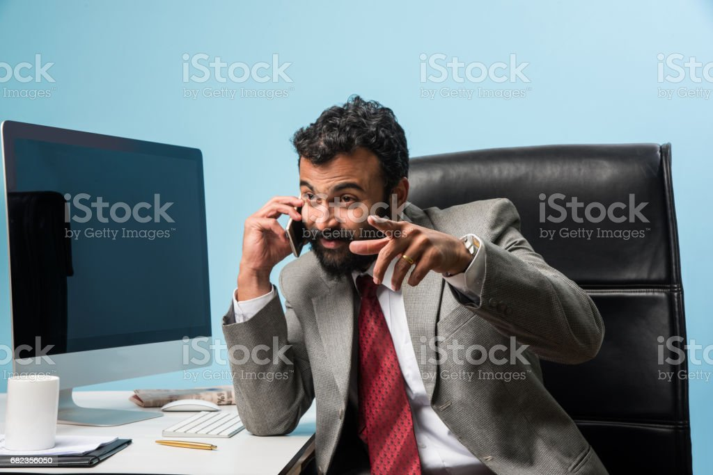 Young Indian businessman in beard busy on phone call while using laptop or computer in office, asian businessman talking using smartphone ロイヤリティフリーストックフォト