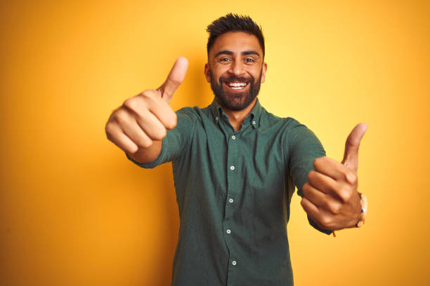 Young indian businessman wearing elegant shirt standing over isolated white background approving doing positive gesture with hand, thumbs up smiling and happy for success. Winner gesture. stock photo