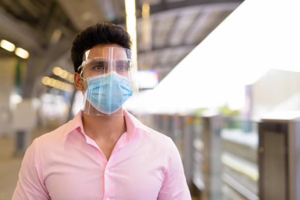Young Indian businessman with mask and face shield waiting at the sky train station stock photo