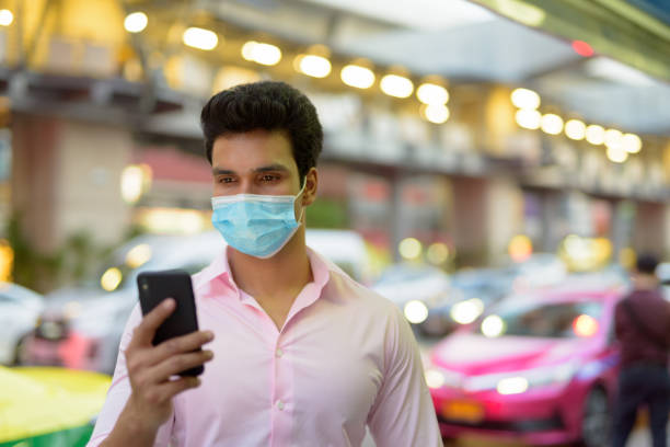 Young Indian businessman with mask using phone in the city streets stock photo