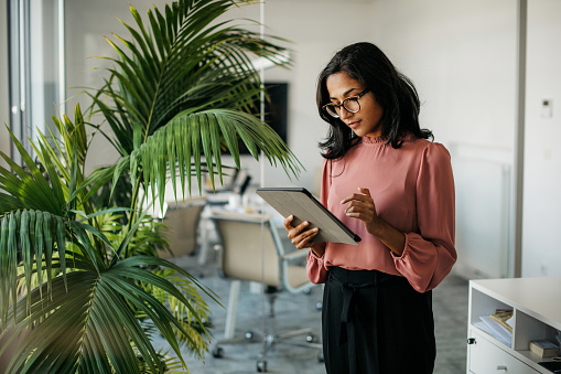Female executive with medium-length black hair wearing eyeglasses and businesswear standing outside modern meeting room and checking data on tablet.