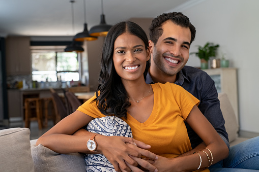 Portrait of happy young indian couple relaxing together on couch. Middle eastern couple cuddling on couch at home in the living room while looking at camera. Portrait of lovely man embracing from behind his beautiful girlfriend sitting in sofa.