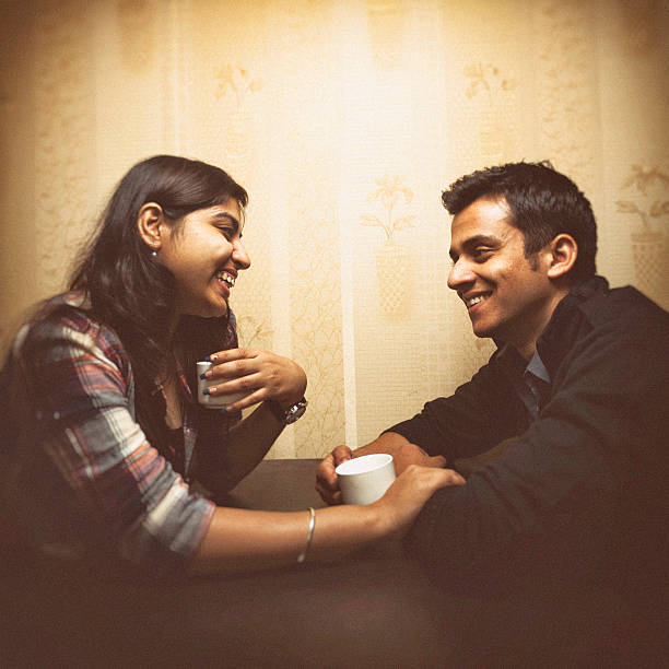 Young Indian couple having coffee in a cafe Attractive young Indian couple having coffee in a cafe together. romance stock pictures, royalty-free photos & images