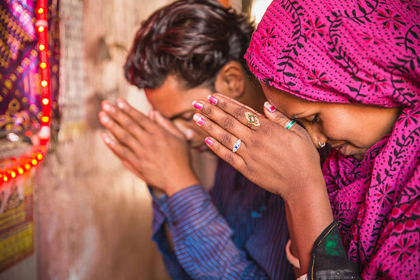 young indian couple praying - hinduism stock photos and pictures