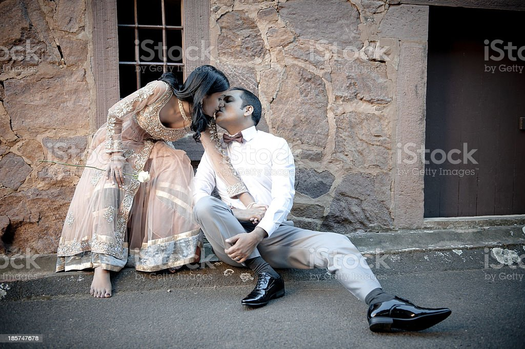Young indian couple sitting on sidewalk kissing stock photo
