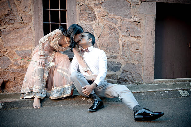 Young indian couple sitting on sidewalk kissing Young indian couple sitting on sidewalk kissing romance stock pictures, royalty-free photos & images