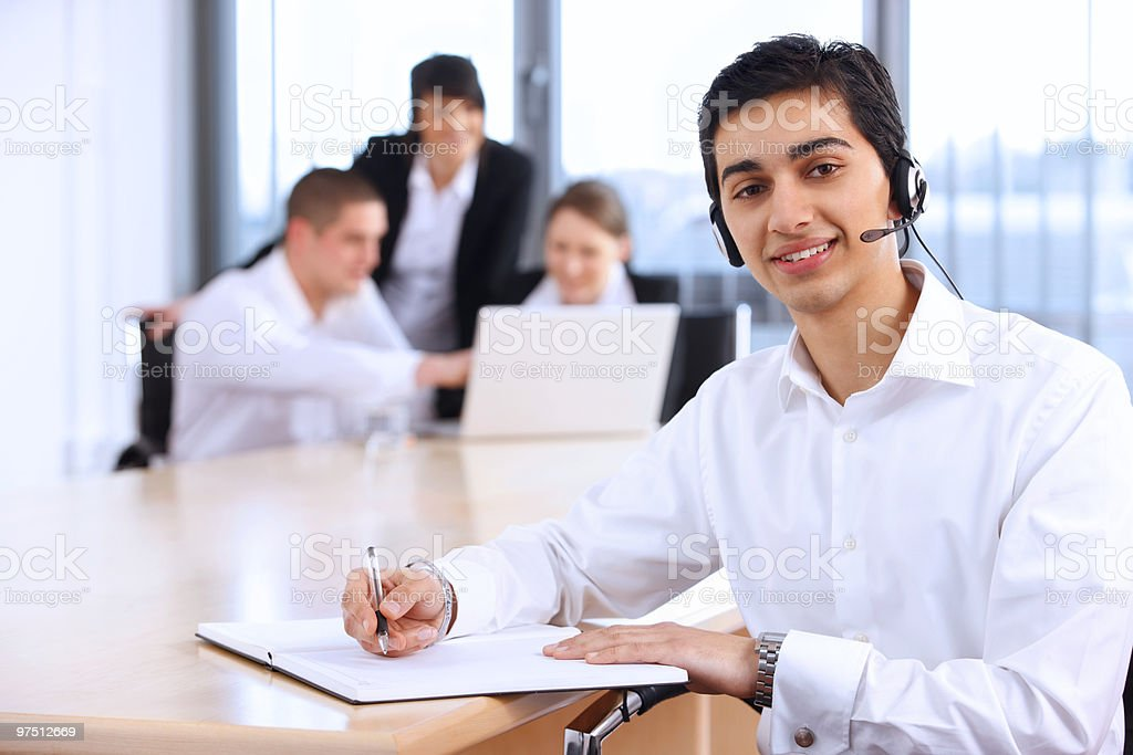 young Indian customer service representative working with colleagues in office royalty-free stock photo