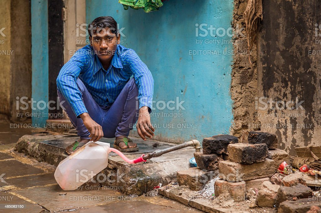 Young Indian man filling water bottle stock photo