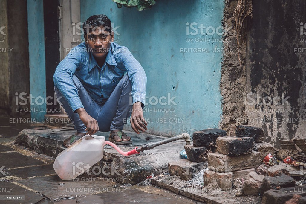 Young Indian man Mumbai, India - January 12, 2015: Young Indian man fills water tank in street. Dharavi slum mostly has drinkable water. Post-processed with grain, texture and colour effect. 2015 Stock Photo