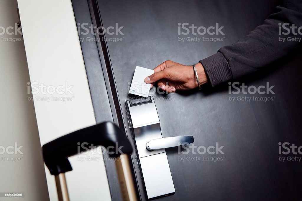 young indian man unlocking his hotel room stock photo
