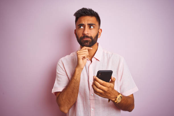 Young indian man using smartphone standing over isolated pink background serious face thinking about question, very confused idea stock photo