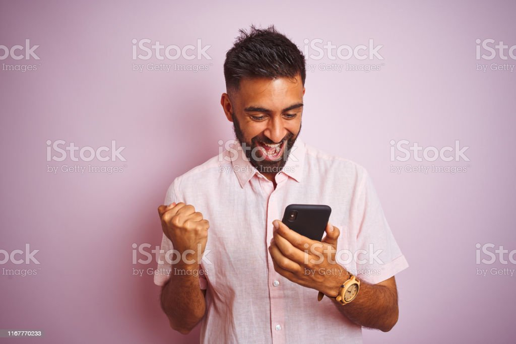 Young indian man using smartphone standing over isolated pink background screaming proud and celebrating victory and success very excited, cheering emotion Young indian man using smartphone standing over isolated pink background screaming proud and celebrating victory and success very excited, cheering emotion Achievement Stock Photo