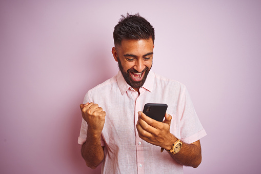 Young Indian Man Using Smartphone Standing Over Isolated Pink Background Screaming Proud And Celebrating Victory And Success Very Excited Cheering Emotion Stock Photo - Download Image Now