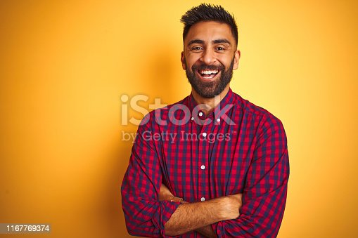 Young indian man wearing casual shirt standing over isolated yellow background happy face smiling with crossed arms looking at the camera. Positive person.