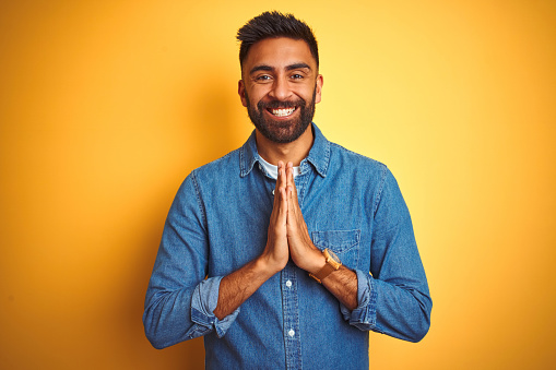 Young indian man wearing denim shirt standing over isolated yellow background praying with hands together asking for forgiveness smiling confident.