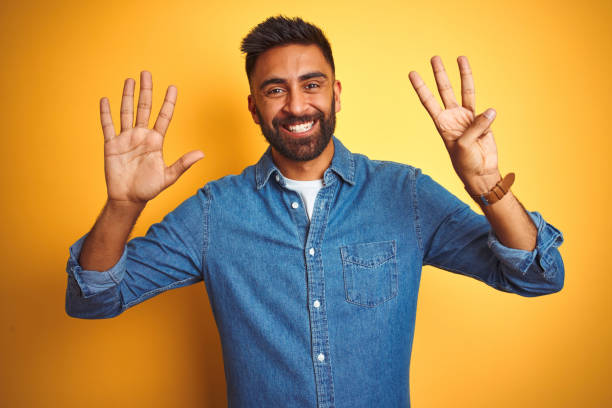 young indian man wearing denim shirt standing over isolated yellow background showing and pointing up with fingers number eight while smiling confident and happy. - number 8 stock pictures, royalty-free photos & images