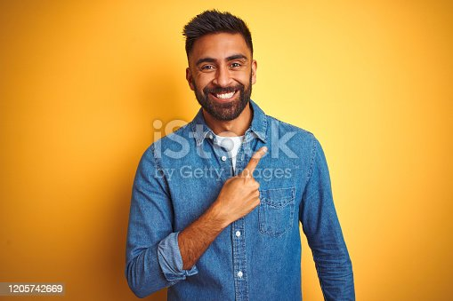 istock Young indian man wearing denim shirt standing over isolated yellow background cheerful with a smile of face pointing with hand and finger up to the side with happy and natural expression on face 1205742669