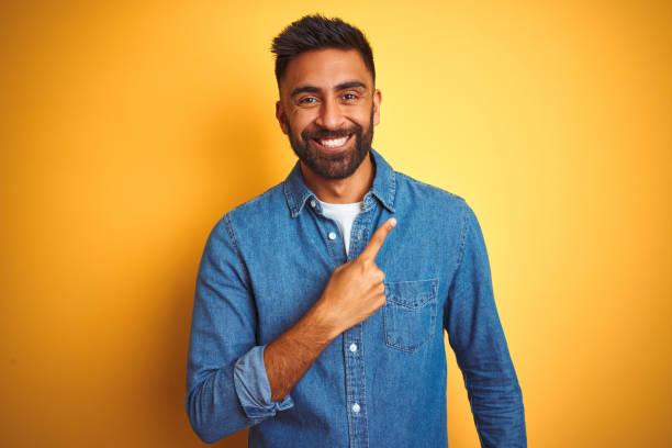 jonge indische mens die denimoverhemd draagt dat zich over geïsoleerde gele achtergrond vrolijk met een glimlach van gezicht dat met hand en vinger tot de kant met gelukkige en natuurlijke uitdrukking op gezicht richt - menselijke vinger stockfoto's en -beelden