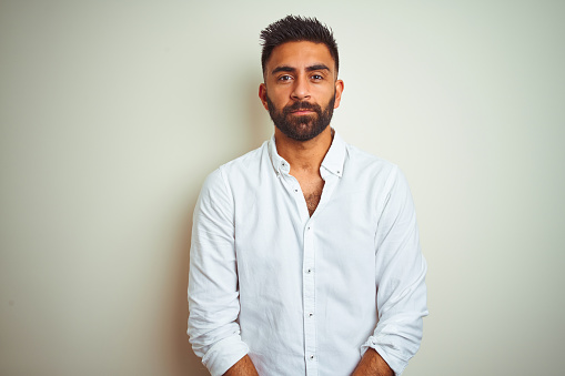 Young indian man wearing elegant shirt standing over isolated white background with serious expression on face. Simple and natural looking at the camera.