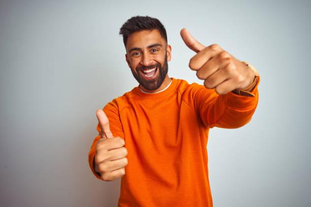 年輕的印度男子穿著橙色毛衣,在孤立的白色背景批准做積極的姿態與手,豎起大拇指微笑和高興的成功。獲勝者手勢。 - 人手指 個照片及圖片檔