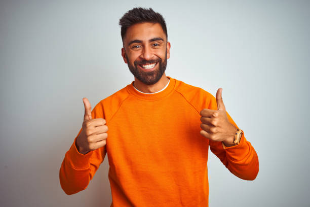 Young indian man wearing orange sweater over isolated white background success sign doing positive gesture with hand, thumbs up smiling and happy. Cheerful expression and winner gesture. stock photo