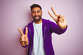 istock Young indian man wearing purple sweatshirt standing over isolated pink background smiling looking to the camera showing fingers doing victory sign. Number two. 1167770989