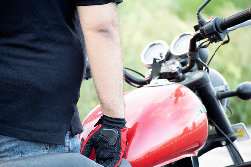Young indian man wearing red riding gloves with protection while holding the handle bars of a motorcycle with a red tank