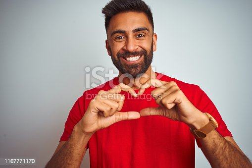 Young indian man wearing red t-shirt over isolated white background smiling in love showing heart symbol and shape with hands. Romantic concept.