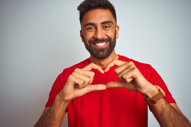 Young indian man wearing red t-shirt over isolated white background smiling in love showing heart symbol and shape with hands. Romantic concept. Young indian man wearing red t-shirt over isolated white background smiling in love showing heart symbol and shape with hands. Romantic concept. red shirt stock pictures, royalty-free photos & images