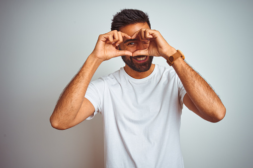 Young indian man wearing t-shirt standing over isolated white background Doing heart shape with hand and fingers smiling looking through sign