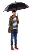 Portrait of young Indian man wearing a smart casual outfit holding an umbrella on white background