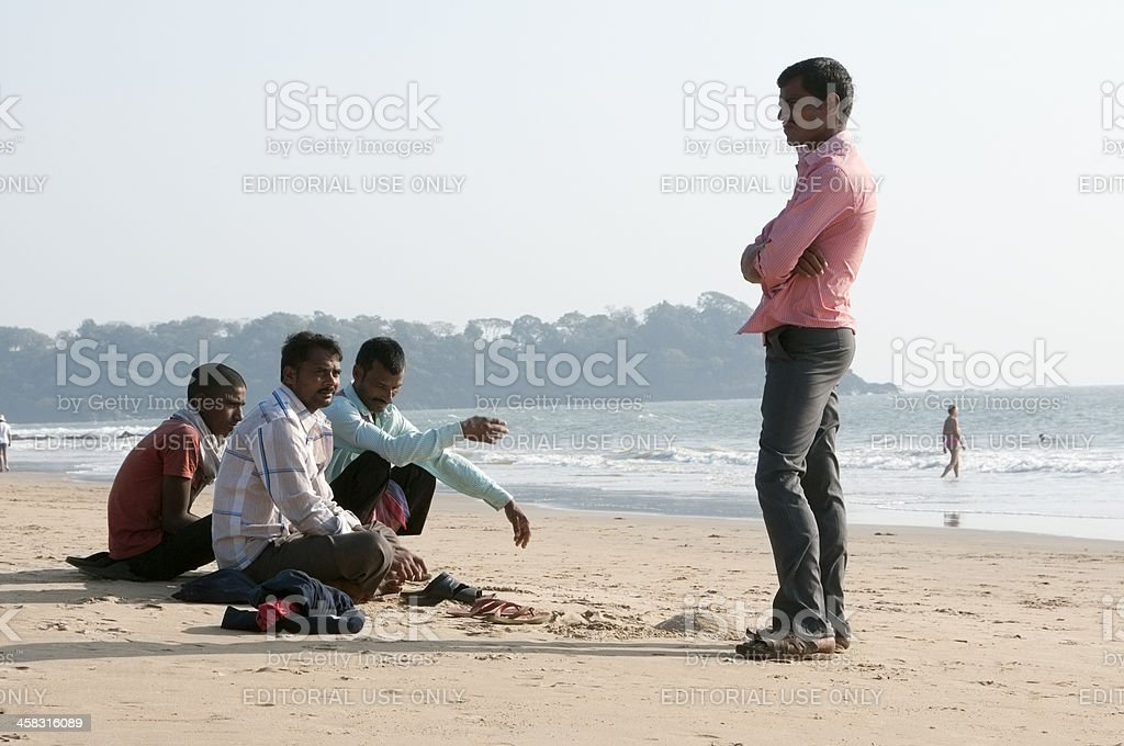 Young Indian men sitting on beach next to ocean royalty-free stock photo