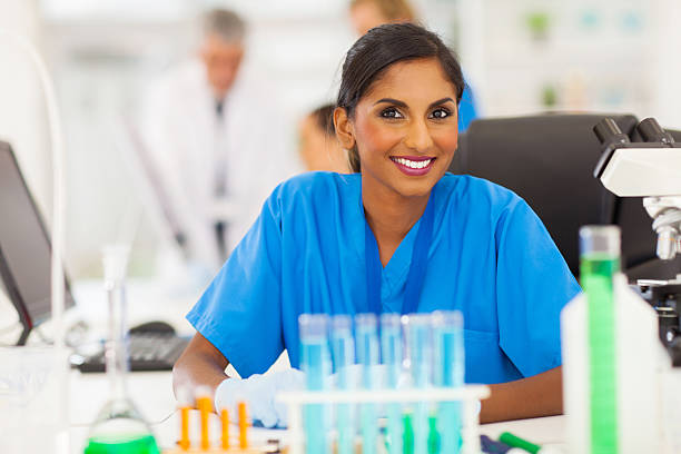 young indian researcher working in lab stock photo