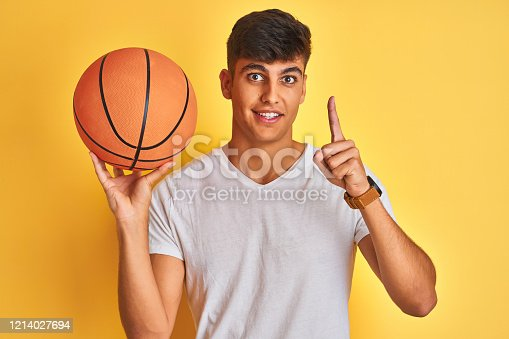 Young indian sportsman holding basketball ball standing over isolated yellow background surprised with an idea or question pointing finger with happy face, number one