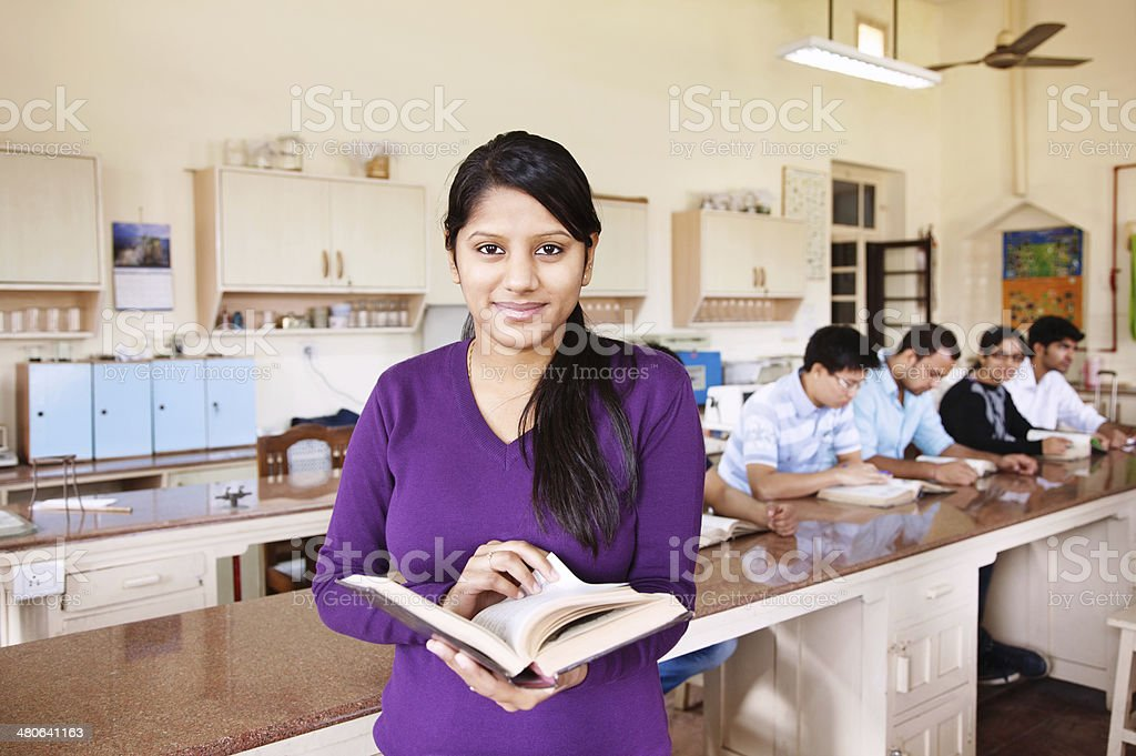 Young Indian student holding books indoors stock photo